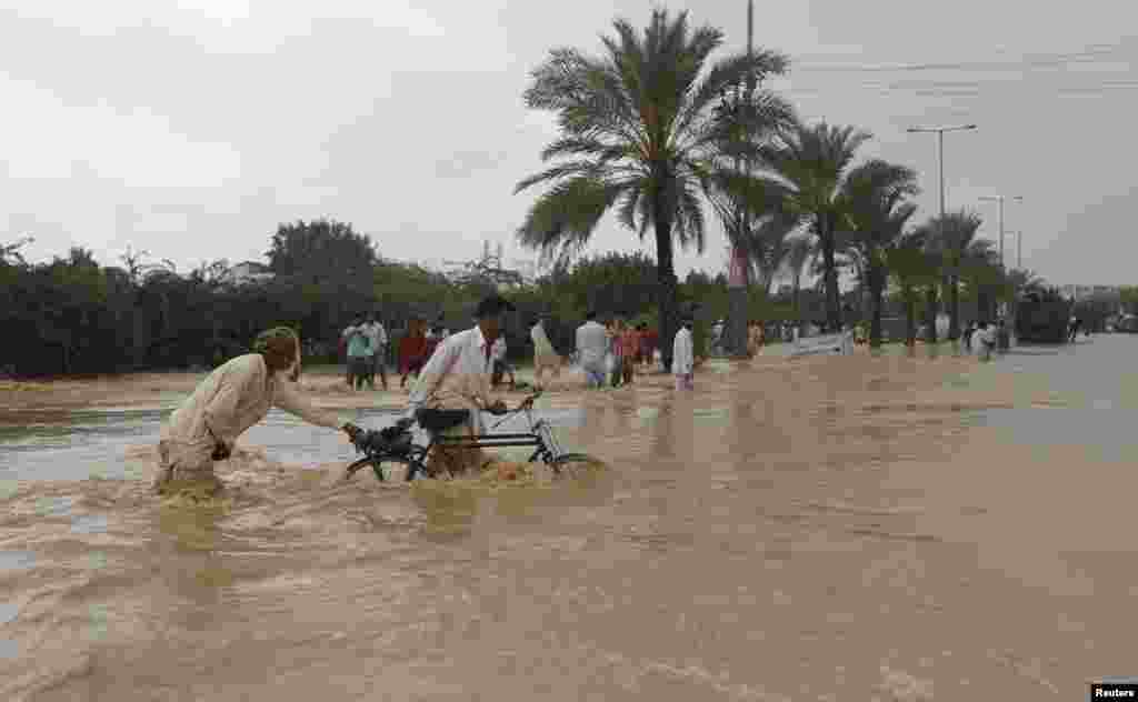 Men push their bicycles through floodwaters on the outskirts of Karachi.
