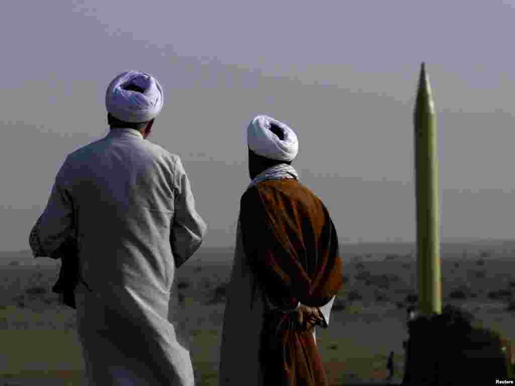 Doi clerici iranieni în apropierea unei rachete sol-sol pregătită de lansare pe un poligon lîngă orașul Qom. Photo by Rauf Mohseni for Reuters.