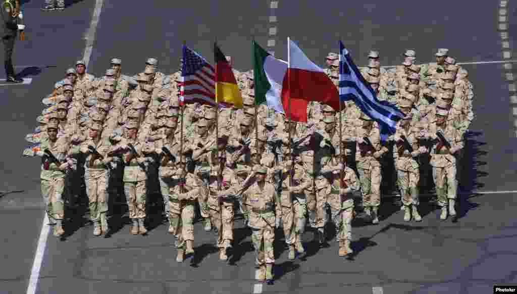 Армянские военнослужащие несут флаги США, Германии, Италии, Польши и Греции на военном параде.