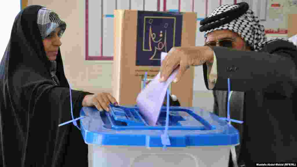 A man casts his ballot in provincial elections under the supervision of a woman election monitor in Karbala.