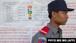 Сайлауға түсіп жатқан саяси партиялар туралы ақпарат ілінген жерде тұрған полиция қызметкері. Мандалай, Мьянма, 7 қараша 2015 жыл.