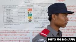 Сотрудник избирательной комиссии Мьянмы стоит у стенда с инструкцией по голосовованию. 7 ноября 2015 года.