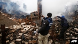 Members of the OSCE's Special Monitoring Mission to Ukraine take pictures of a destroyed house in Avdiyivka after heavy shelling by pro-Russia separatists