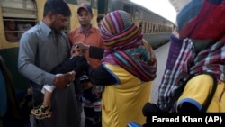 A health worker gives a polio vaccine to a child at a railway station, days after Pakistan launched an anti-polio campaign across the country, despite threats from the Taliban, in Karachi, Pakistan on Thursday, January 18.