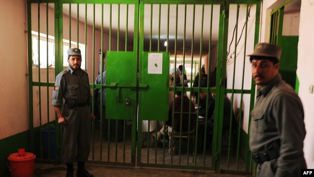 Prison officials stand guard during a visit by local and international media at a Kabul prison.