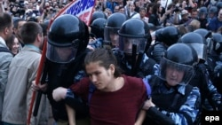 Russian police detain a protester at an unauthorized opposition rally in central Moscow on June 12.