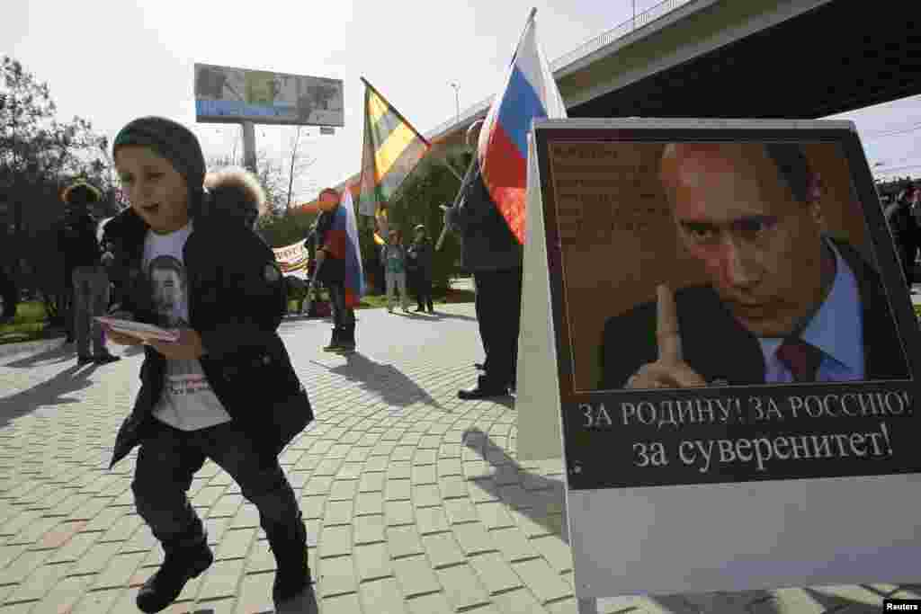 "A boy passes a poster of Russian President Vladimir Putin reading ""For Motherland, for Russia, for Sovereignty"" as he runs to distribute pamphlets to visitors. (REUTERS/Michael Caronna)"