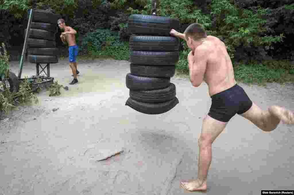 Men pummelling stacks of tires. The gym is free, and never closes.