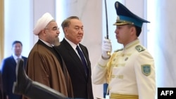 Kazakh President Nursultan Nazarbaev (center) and his Iranian counterpart Hassan Rohani (left) review a guard of honor during a welcoming ceremony before their meeting in Astana on December 22.