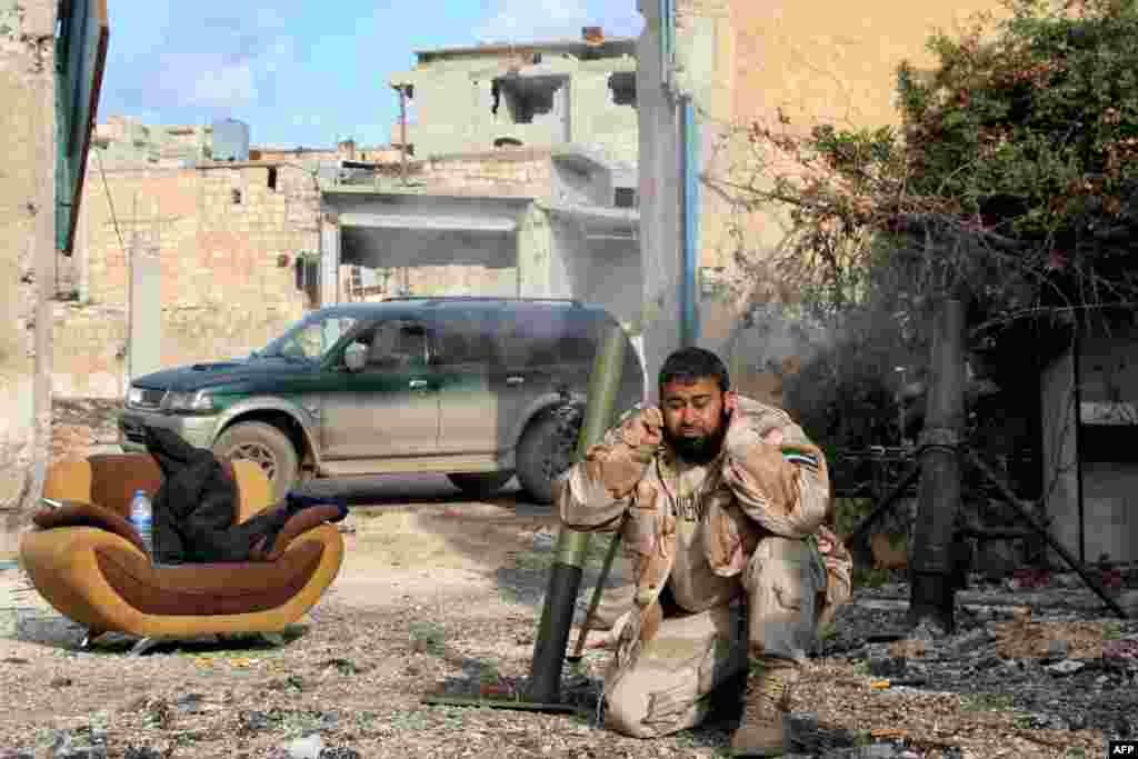A fighter fires mortar shells from a rebel-held area toward Syrian pro-regime positions during the battle for control of the Handarat region, located just north of Aleppo. (AFP/Karam al-Masri)