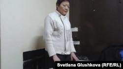 Умит Нуртазина за столом у дверей своей квартиры. Астана, 24 декабря 2013 года.