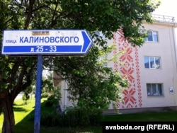 Расейскамоўны паказальнік вуліцы Каліноўскага на тле дома з арнамэнтам