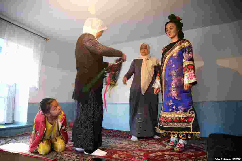 После того, как прическа уложена, девушке помогают одеться. Яркий костюм дунганской невесты состоит из двух рубашек - короткой и длинной, безрукавки, праздничной накидки, штанов, парчовых носков и специальных свадебных туфель. Все компоненты одежды украшены ручной вышивкой.