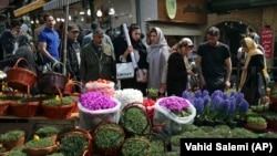 In this Monday, March 19, 2018 photo, Iranians shop for hyacinths, garlic, sprouts and other items used to celebrate the Iranian New Year, at the Tajrish traditional bazaar in northern Tehran.