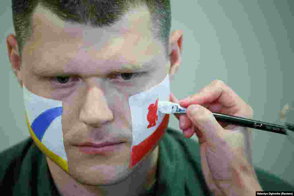 An officer with the Ukrainian State Border Guard Service has his face painted in the colors of both Champions League finalists, Liverpool and Real Madrid, as he prepares to meet soccer fans at the Boryspil International Airport outside Kyiv on May 25.