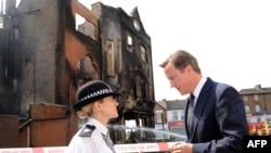 Британский премьер Дэвид Кэмерон беседует с полицейским в пригороде Лондона Кройдоне. 9 августа 2011 г