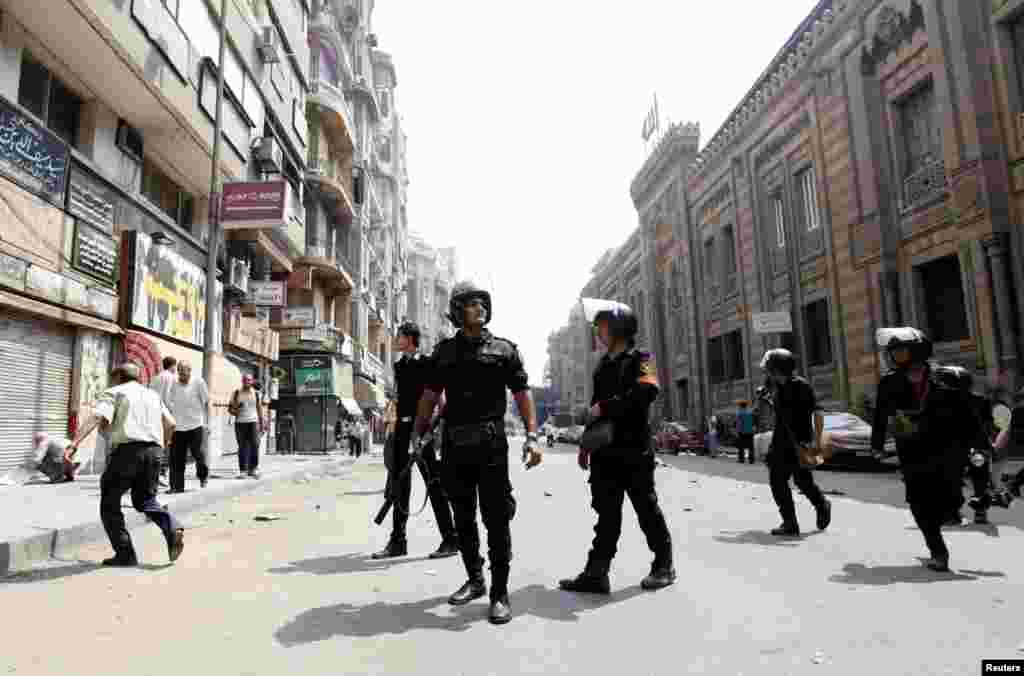 Police walk in the middle of a street during clashes in central Cairo on August 13. (Reuters/Mohamed El Ghany)