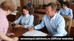 Кандидаты Александра Романенко (л) и Ярослав Яковенко (п) на заседании Севастопольской городской избирательной комиссии