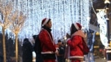 KAZAKHSTAN -- People dressed as Santa Claus stay next to the Christmas illuminations in Almaty, Kazakhstan December 20, 2018