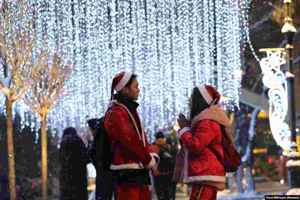 People dressed as Santa Claus stand next to Christmas lights in Almaty, Kazakhstan. (Reuters/Pavel Mikheyev )
