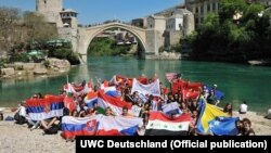 Студэнты на фоне сымбалю Мостара — старога моста