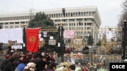 People pray for those killed in the violence outside the gates of the government building in Bishkek last April.