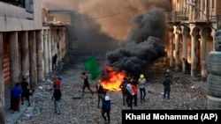 Anti-government protesters start a fire while security forces close Rasheed Street during clashes in Baghdad on November 28.