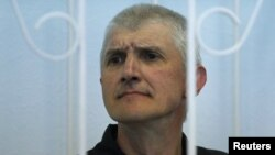 Platon Lebedev looks out from the defendant's box as he attends a court hearing to consider a request for parole in Velsk in Arkhangelsk in July 2011.