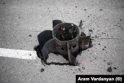 Aripile cozii unei rachete mari, înfipte în asfalt pe o stradă din Stepanakert