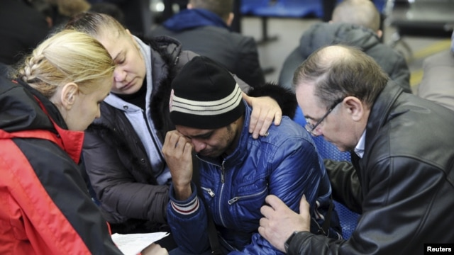 A psychologist of the Russian Emergency Situations Ministry (left) speaks with a relative (center) of a victim of the crashed FlyDubai Boeing 737-800 at the airport of Rostov-On-Don on March 19.