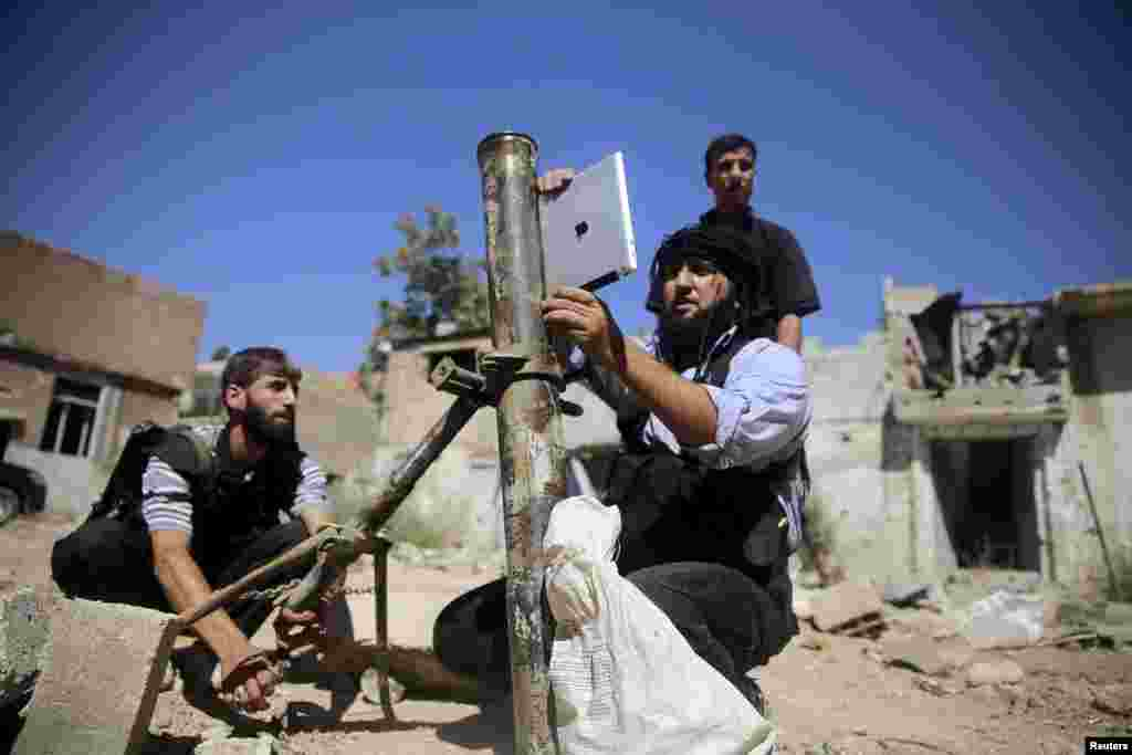 A member of the Ansar Dimachk Brigade, part of the rebel Free Syrian Army battling forces loyal to Syrian leader Bashar al-Assad, uses an iPad during preparations to fire a homemade mortar at one of the battle front in Damascus. (Reuters/Mohamed Abdullah)