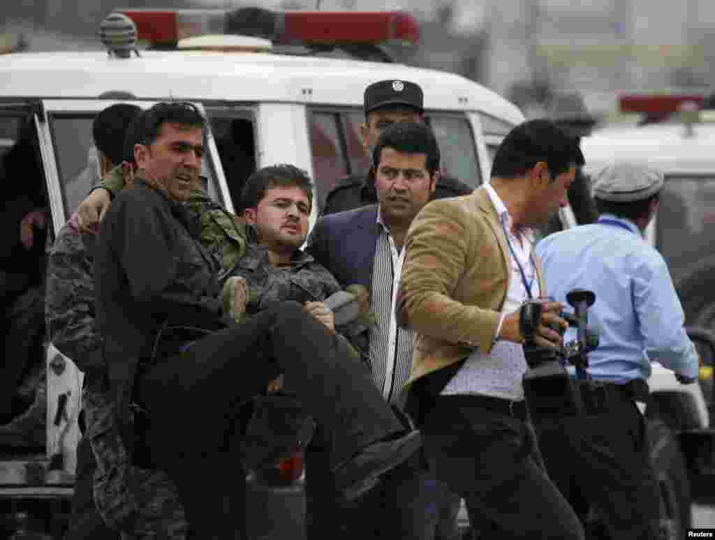 Afghan security forces carry an injured security officer after the attack.