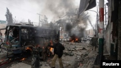A policeman calls for help as he stands near a burning site after a bomb blast in Quetta on March 14, 2014.