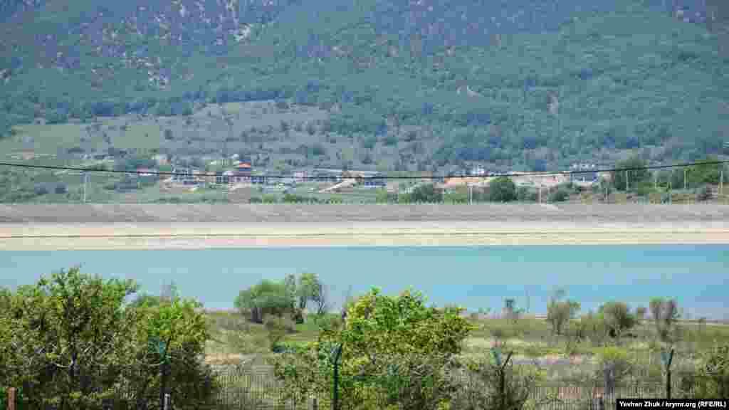 Дамба в південно-західній частині водосховища, вдалині видніються новозбудовані котеджі на полі поруч із селом Широке