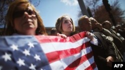 U.S. -- Jaime Caputo (C) holds an American flag outside the funeral for 29-year-old Krystle Campbell, who was one of three people killed in the Boston Marathon bombings, in Medford, Massachusetts, 22Apr2013