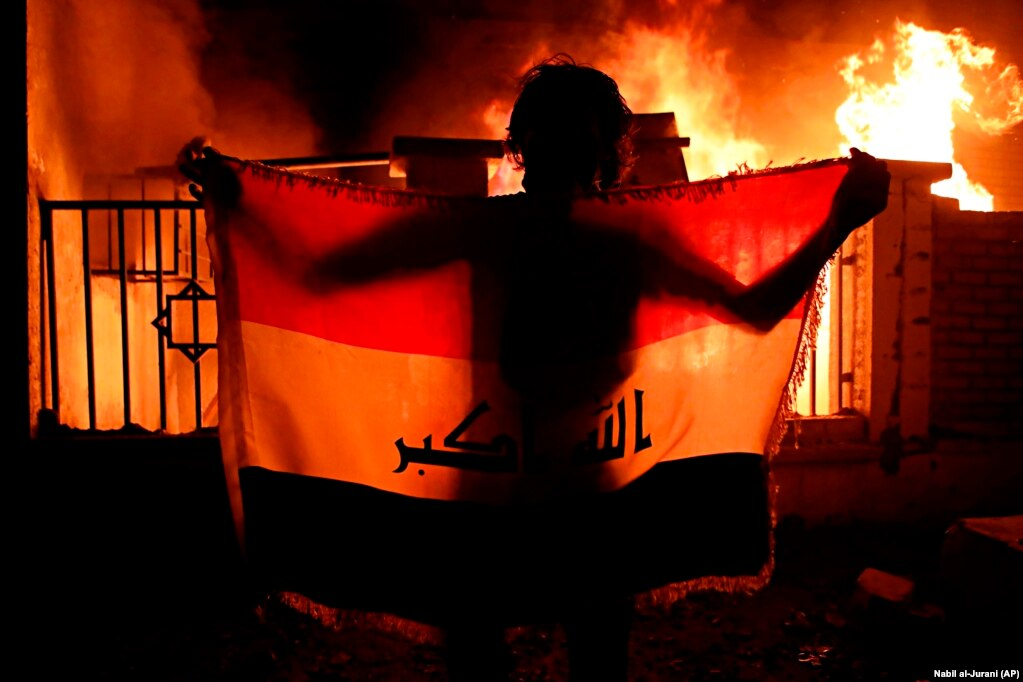 A man holds an Iraqi national flag while protesters burn a municipal complex during protests demanding better public services and jobs in the city of Basra, 550 kilometers southeast of Baghdad. (AP/Nabil al-Jurani)