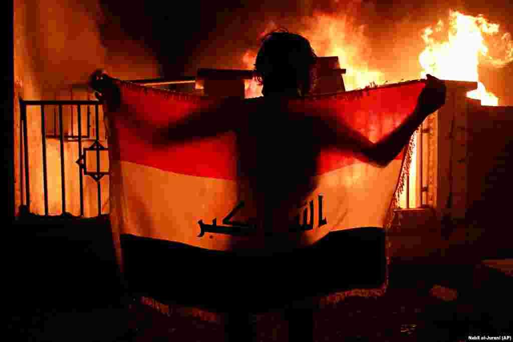 Мужчына трымае іракскі нацыянальны сьцяг на фоне муніцыпальнага комплексу ў Басры, які падпалілі пратэстоўцы, патрабуючы лепшых грамадзкіх паслугаў і больш працоўных месцаў, 5 верасьня.