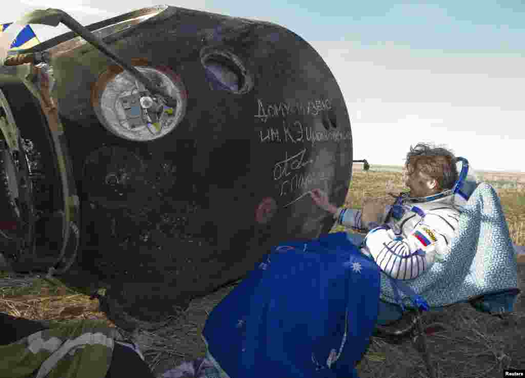 Padalka, who piloted the spacecraft back to Earth, was the first to be pulled out of the charred Soyuz capsule. Here, he signs his name on the side of the capsule, which will be displayed at the Tsiolkovsky Museum in the town of Kaluga, southwest of Moscow.