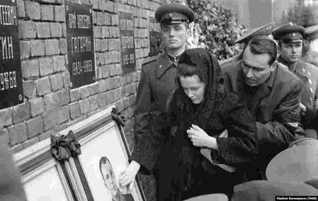 Gagarin's widow, Valentina Gagarina, touches a portrait of her husband at the Kremlin wall during the funeral.