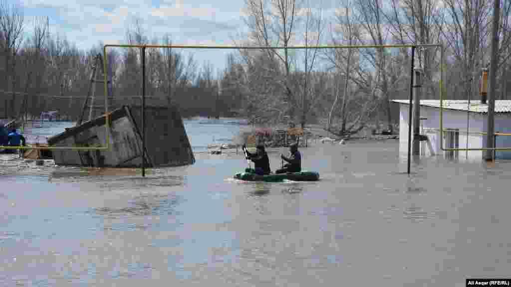 Жители подтопленных районов передвигаются на лодке.