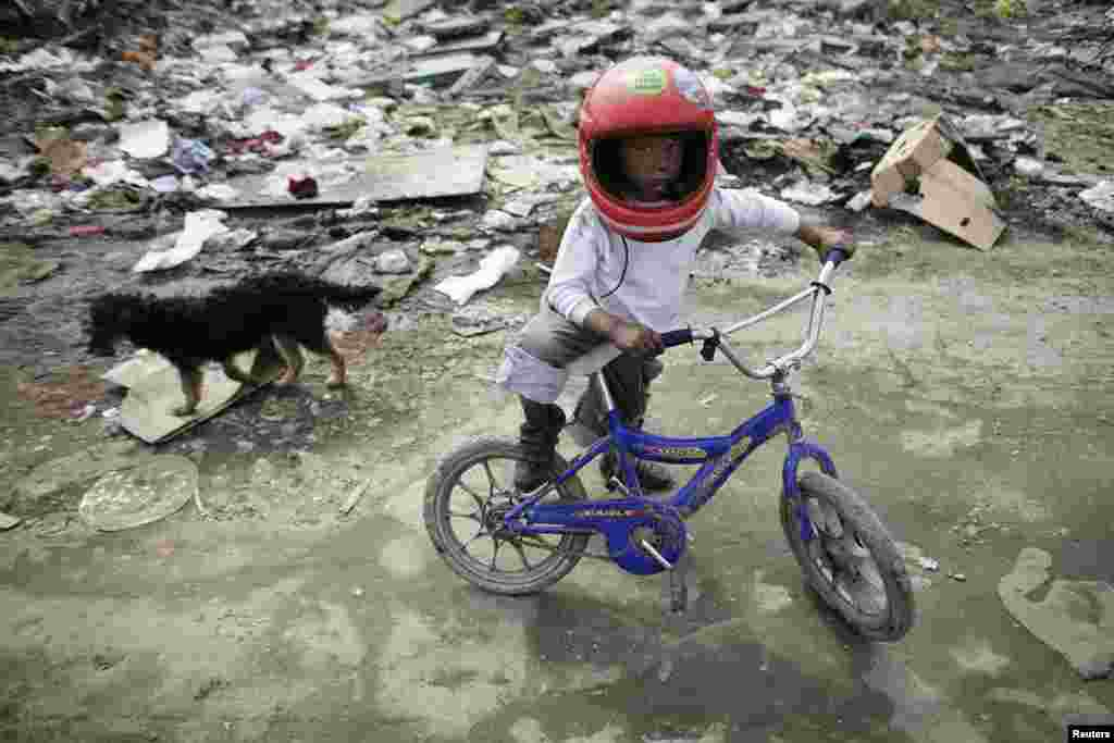 A boy rides a bike in a Romany settlement in Sarajevo's suburb of Butmir, Bosnia-Herzegovina.