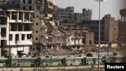 Автобуси для евакуації людей на тлі зруйнованого Алеппо
