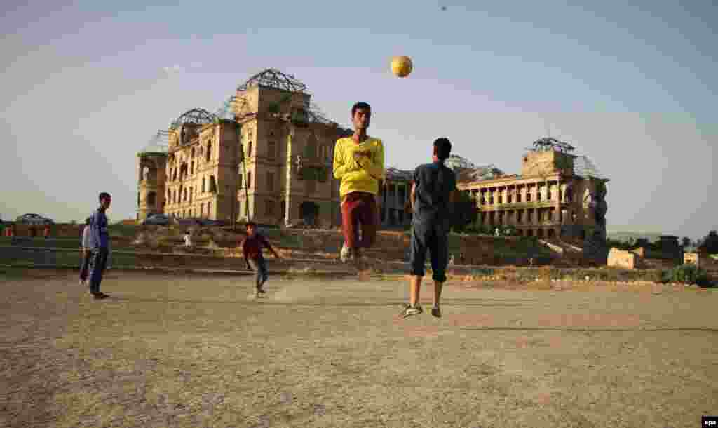 Afghan boys play with a soccer ball, beside the war-ravaged Dar-ul-Aman palace, on the outskirts of Kabul. (epa/Hedayatullah Amid)