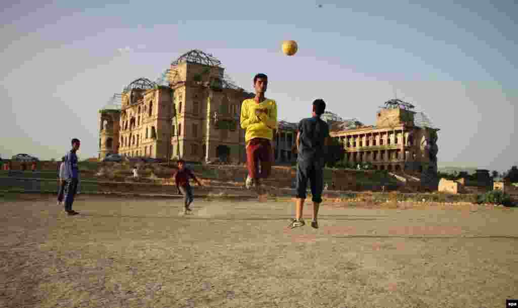 Afghan boys play with a soccer ball, beside the war-ravaged Dar-ul-Aman palace, on the outskirts of Kabul. (epa/Hedayatullah Amid)