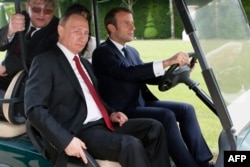 Емманюель Макрон возить Володимира Путіна по Версальському парку. 29 травня 2017 року