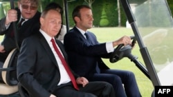 French President Emmanuel Macron (right) drives an electric golf cart with Russian President Vladimir Putin through the garden of the Versailles Palace following a meeting in May.