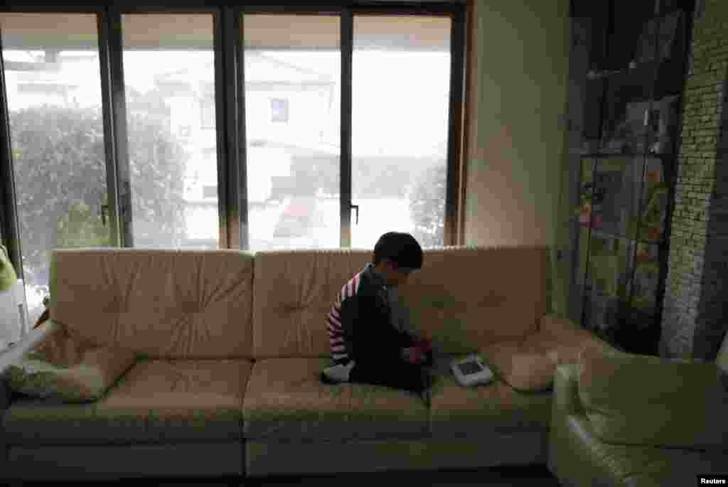 Seven-year-old Masyoshi Kaneta plays video games at home in Koriyama.