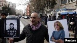 Demonstrant nosi slike francuskog fotografa Remija Ochlika i američke novinarka Marie Colvin koji su ubijeni u Siriji 22. februara 2012.