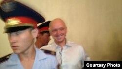 """Тіркелмеген """"Алға"""" партиясының жетекшісі Владимир Козловты сот залына әкеле жатыр."""