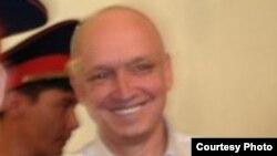 """Тіркелмеген """"Алға"""" партиясының жетекшісі Владимир Козловты сот залына әкеле жатыр. Ақтау, 16 тамыз 2012 жыл. Фото Twitter желісінен алынды."""